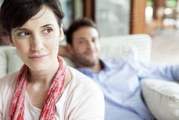 Woman looking away dreamily, man relaxing in background Royalty-free stock photo