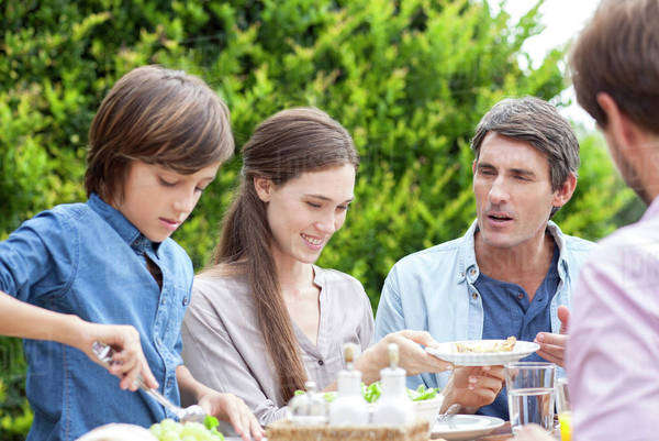 Family eating together at outdoor gathering Royalty-free stock photo