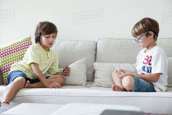 Boys sitting on sofa playing cards Royalty-free stock photo