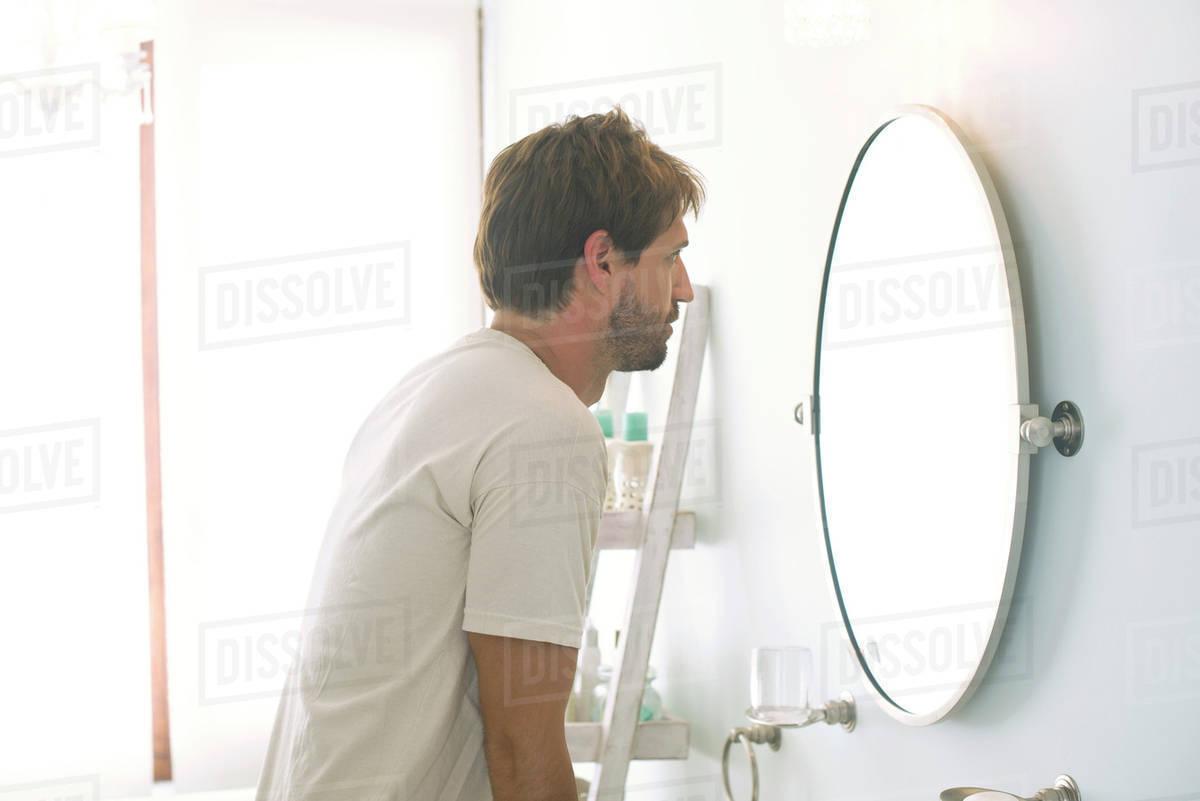 man looking at self in bathroom mirror stock photo dissolve