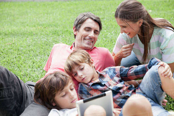 Family with two children spending afternoon at park, young boys using digital tablet Royalty-free stock photo