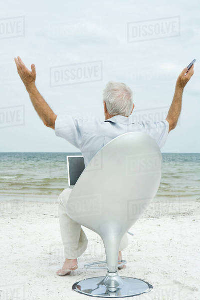 Senior man sitting in chair on beach, using laptop, arms in air, rear view Royalty-free stock photo
