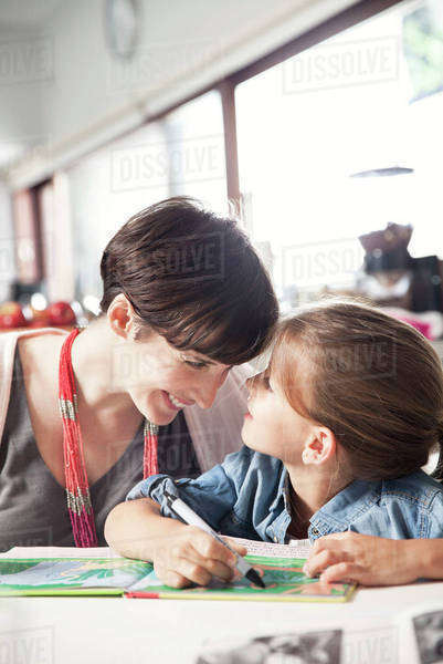 Mother and young daughter reading together, affectionately touching foreheads Royalty-free stock photo
