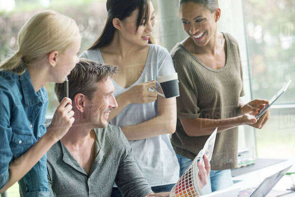 Colleagues having lighthearted time while browsing color swatch catalog Royalty-free stock photo