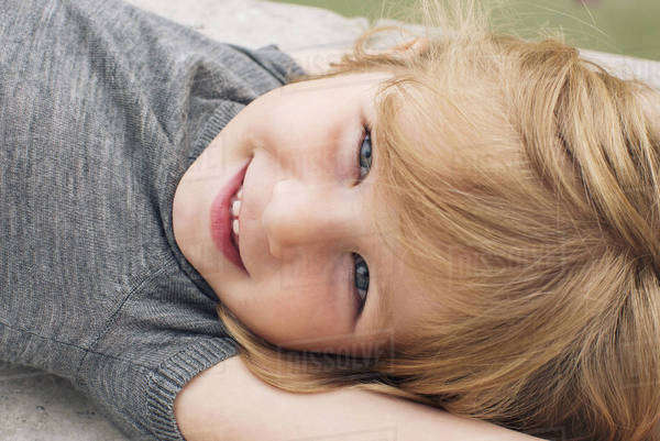 Little girl lying on her back, smiling, portrait Royalty-free stock photo