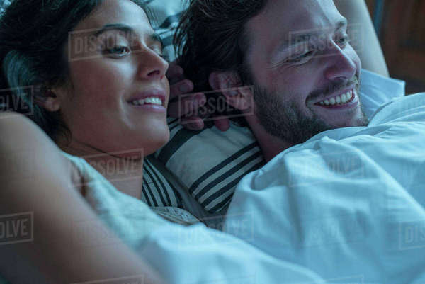 Couple watching tv together in bed Royalty-free stock photo