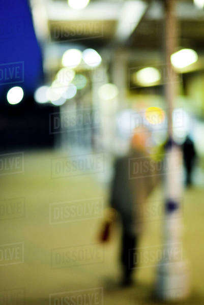 Pedestrian walking at night, defocused Royalty-free stock photo