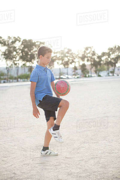 Boy kneeing soccer ball in sand Royalty-free stock photo