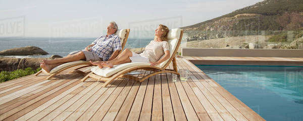 Older couple relaxing in lawn chairs by pool Royalty-free stock photo