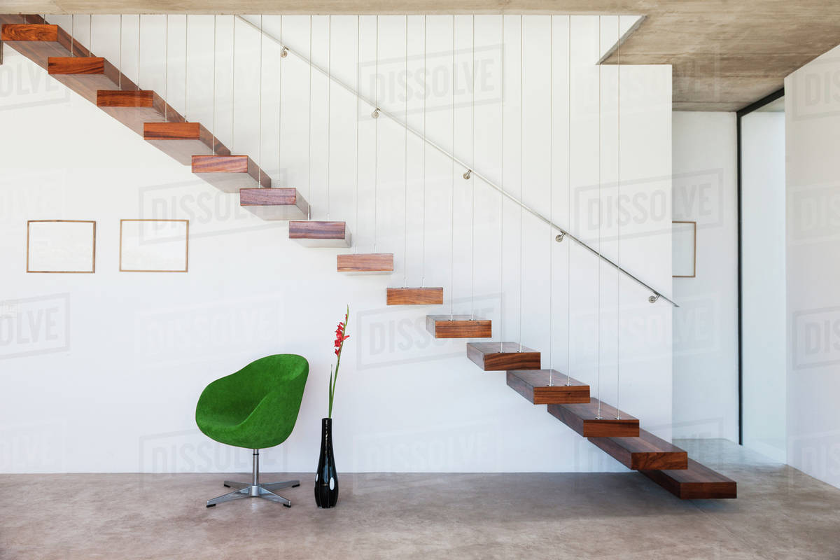 Chair under floating staircase in modern house
