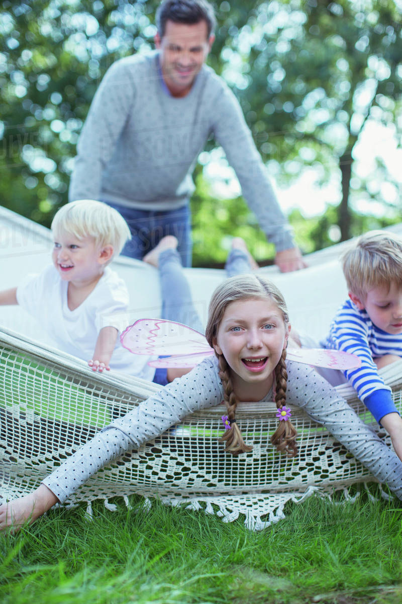 Father pushing children in hammock outdoors Royalty-free stock photo