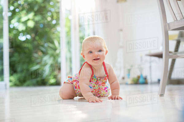 Baby girl crawling on kitchen floor Royalty-free stock photo