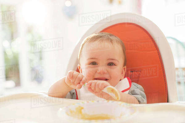 Baby boy eating in high chair Royalty-free stock photo