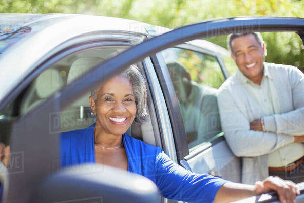 Portrait of happy senior couple inside and outside of car Royalty-free stock photo
