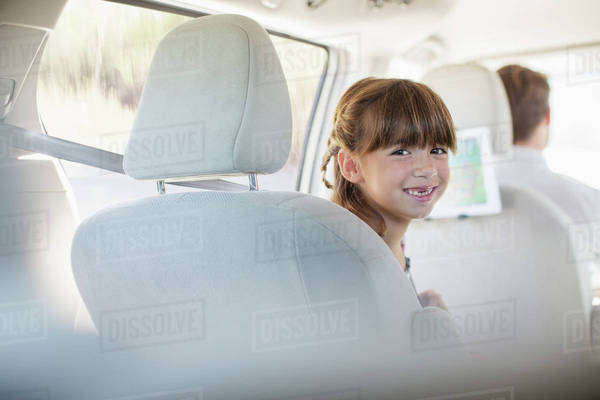 Portrait of smiling girl in back seat of car Royalty-free stock photo