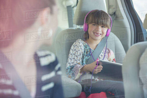 Mother turning and smiling at daughter with headphones and digital tablet in back seat of car Royalty-free stock photo