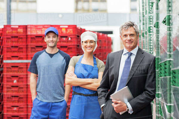 Portrait of supervisor and workers in food processing plant Royalty-free stock photo