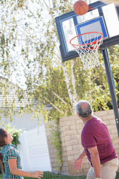 Grandfather and granddaughter playing basketball Royalty-free stock photo