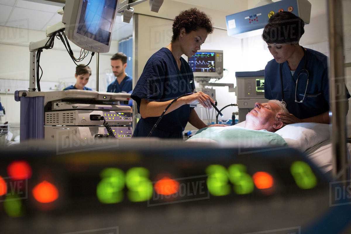 Doctors attending patient in intensive care unit, monitoring equipment in foreground Royalty-free stock photo