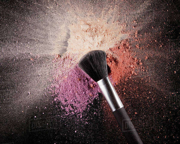 Makeup brush over multicolor blush splatter Royalty-free stock photo