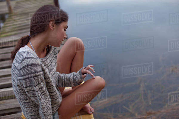 Pensive woman sitting on dock over lake Royalty-free stock photo