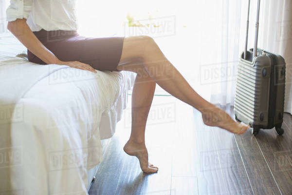 Businesswoman taking shoes off in hotel room Royalty-free stock photo