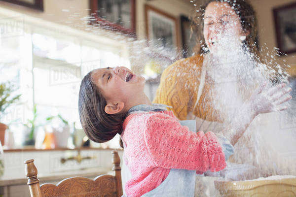 Mother and daughter playing with flour in the kitchen  Royalty-free stock photo