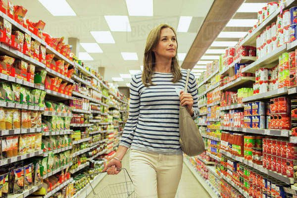 Woman shopping in grocery store aisle Royalty-free stock photo