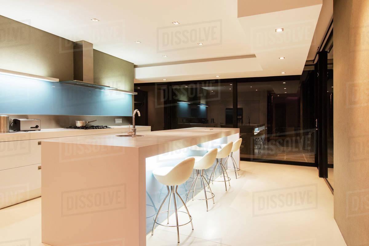 Astonishing Modern White Kitchen With Kitchen Island And Stools Illuminated At Night Stock Photo Machost Co Dining Chair Design Ideas Machostcouk