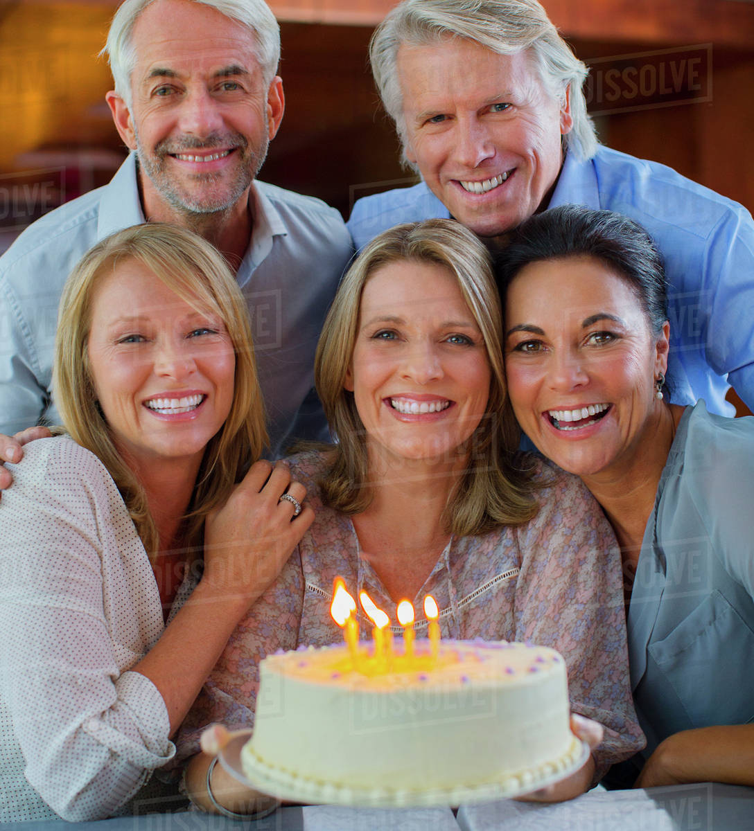 Portrait Of Smiling Mature Men And Women With Birthday Cake Stock