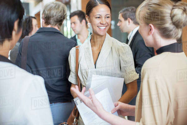 Portrait of two smiling women holding files and talking, standing in crowded lobby Royalty-free stock photo