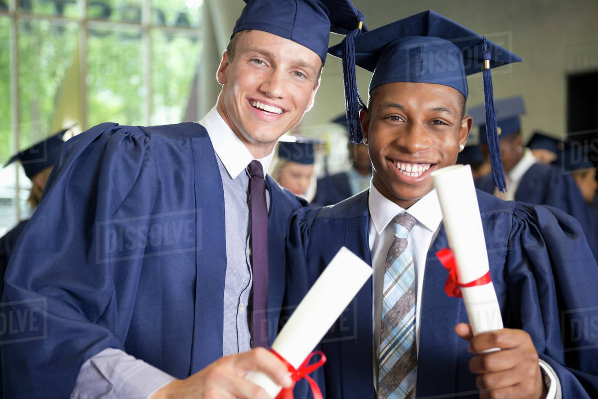a1236effa56 Two laughing male students in graduation clothes holding diplomas ...