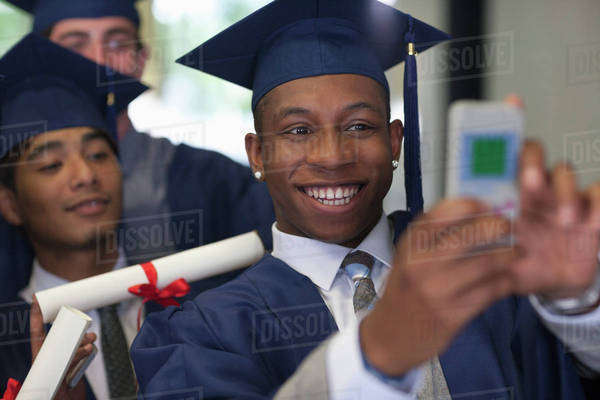 Smiling male student wearing graduation clothes taking selfie with friends Royalty-free stock photo