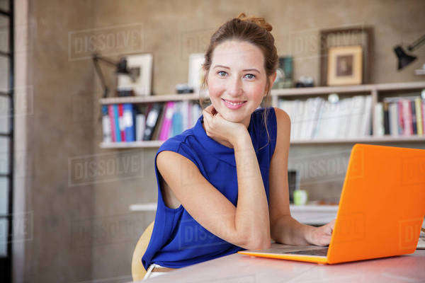 Portrait of young woman with orange laptop sitting in home office Royalty-free stock photo