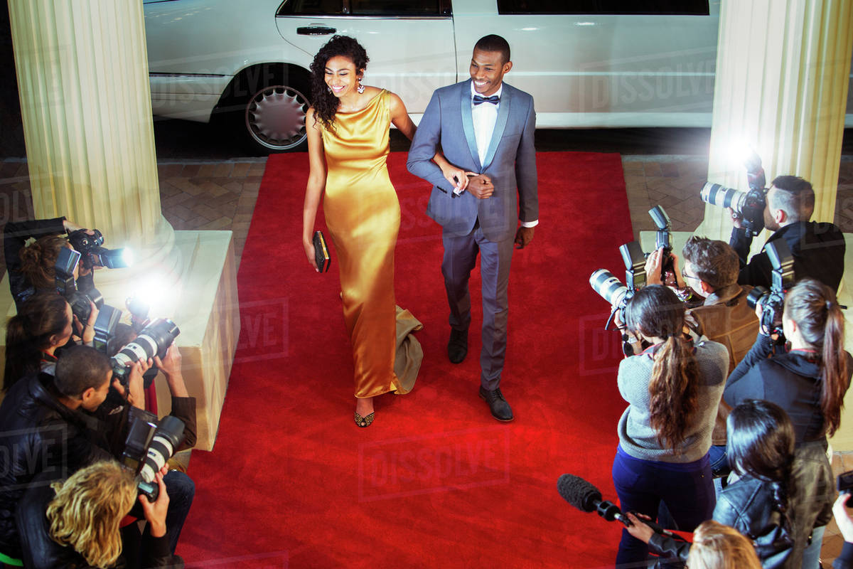 Celebrity Couple Arriving At Red Carpet Event And Being Photographed