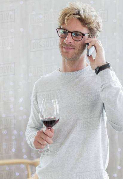 Man drinking red wine and talking on cell phone Royalty-free stock photo