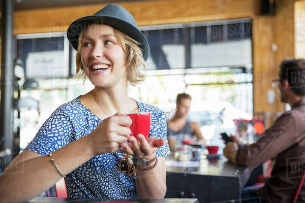 Smiling woman drinking coffee looking over shoulder in cafe Royalty-free stock photo