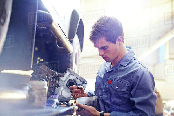 Mechanic examining part in auto repair shop Royalty-free stock photo