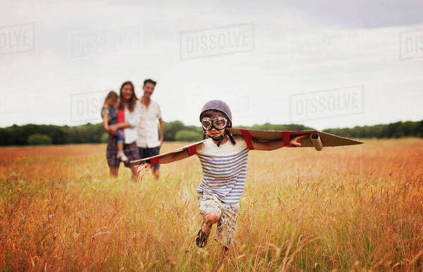 Playful boy with wings in aviator's cap and flying goggles in field Royalty-free stock photo
