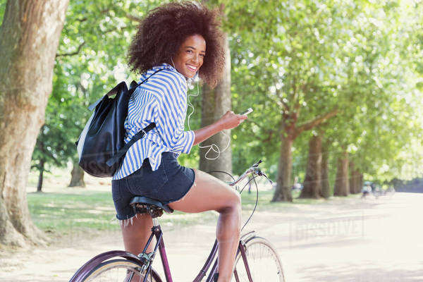 Portrait smiling woman riding bicycle with mp3 player and headphones in park Royalty-free stock photo
