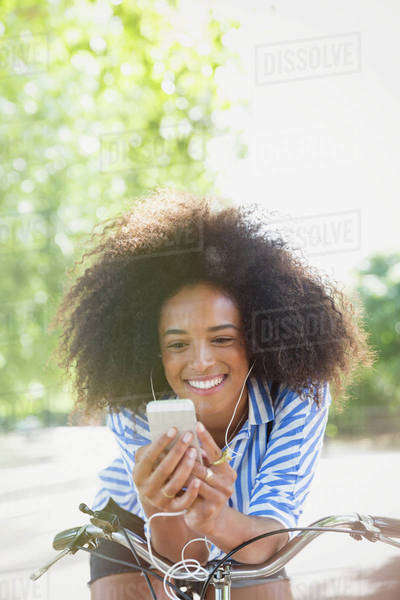 Smiling woman with afro listening to music with headphones and mp3 player on bicycle Royalty-free stock photo