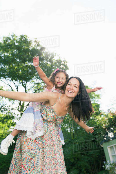 Portrait carefree mother piggybacking daughter with arms outstretched Royalty-free stock photo
