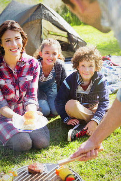 Family watching father barbecuing at campsite grill Royalty-free stock photo