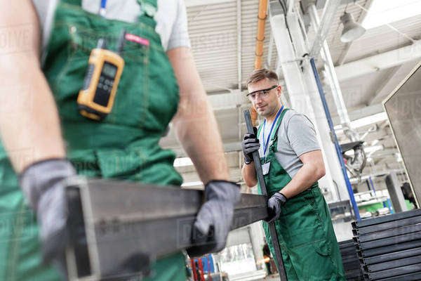 Workers carrying steel part in factory Royalty-free stock photo