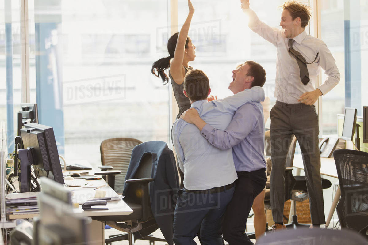 Exuberant business people celebrating and jumping in office Royalty-free stock photo
