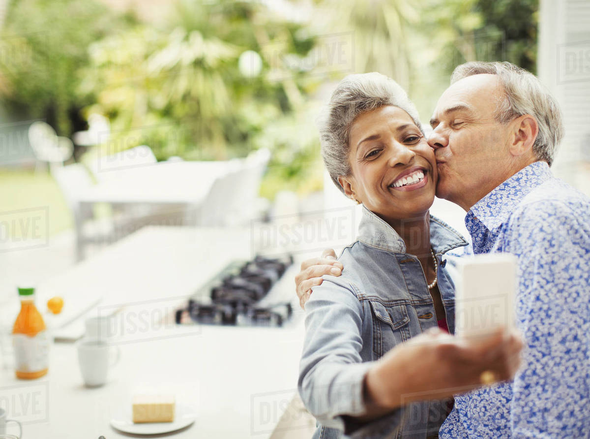 affectionate mature couple kissing taking selfie in kitchen - stock