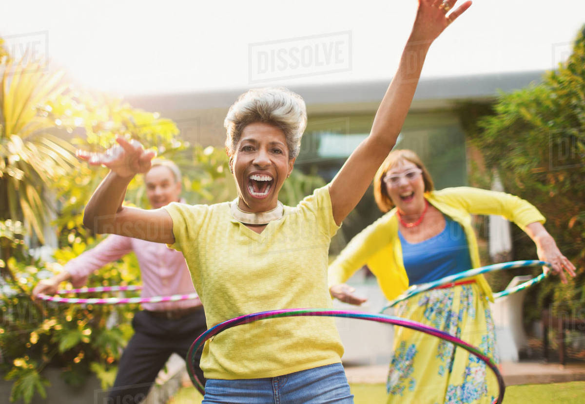 Portrait playful mature adults spinning with plastic hoops in garden Royalty-free stock photo