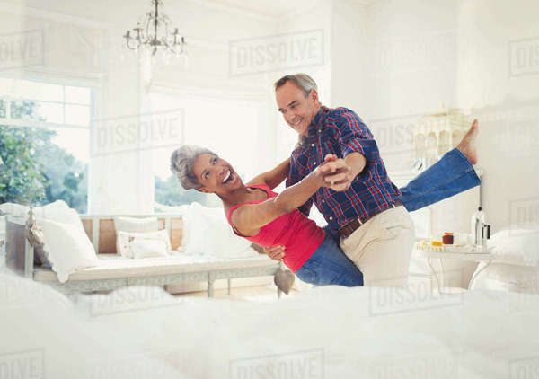 Playful mature couple dancing in living room Royalty-free stock photo