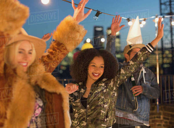 Young adult friends dancing and enjoying rooftop party Royalty-free stock photo