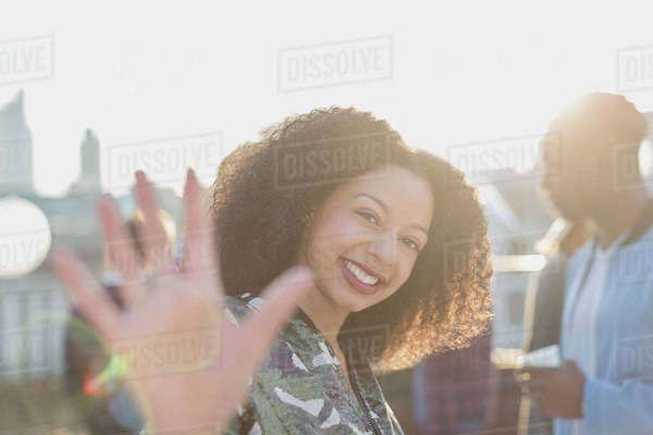 Portrait smiling woman waving at rooftop party Royalty-free stock photo